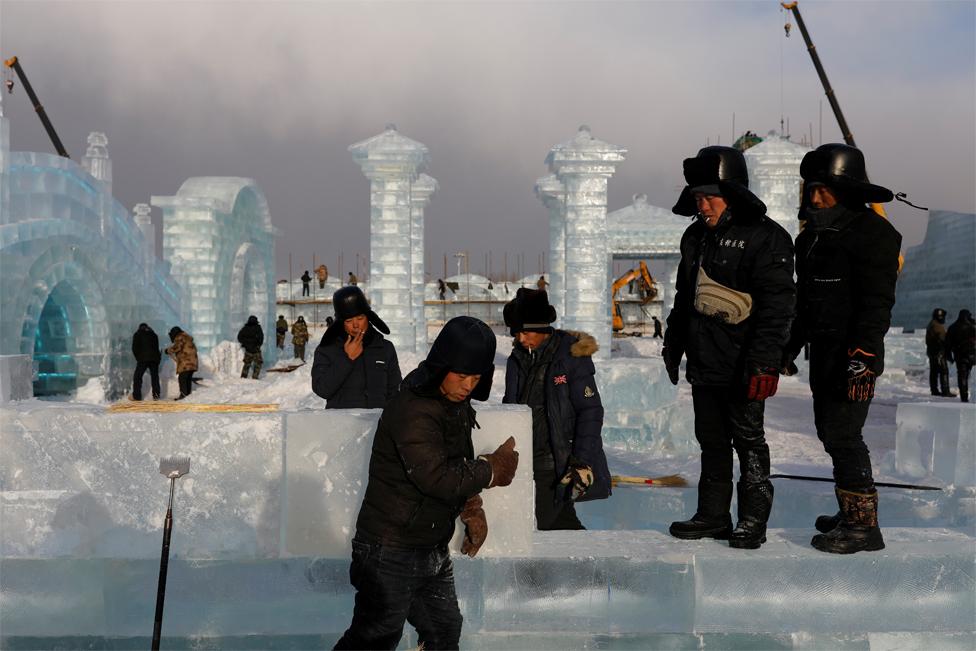 Para pekerja merokok saat membangun struktur es di lokasi Festival Es dan Salju Internasional Harbin