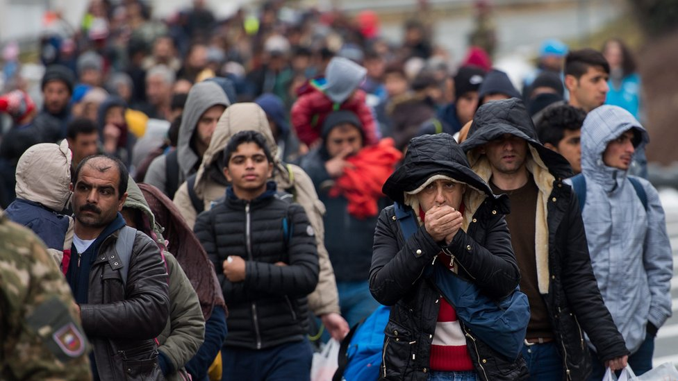 Refugees and migrants walk down a road to cross the Slovenian-Austrian border