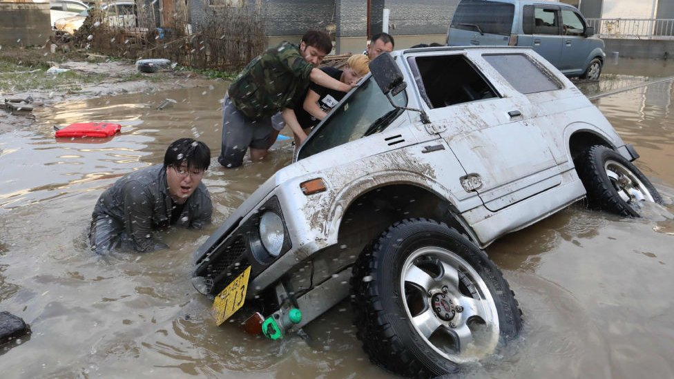 Residents try to upright a vehicle stuck in a flood-hit area in Kurashiki