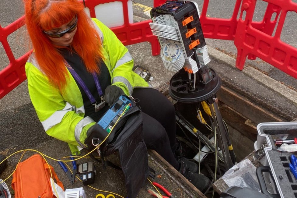 A female Openreach engineer wearing a high-vis vest examines a device in her lap tat is plugged into equipment coming out of the road where a steel plate has been removed for access