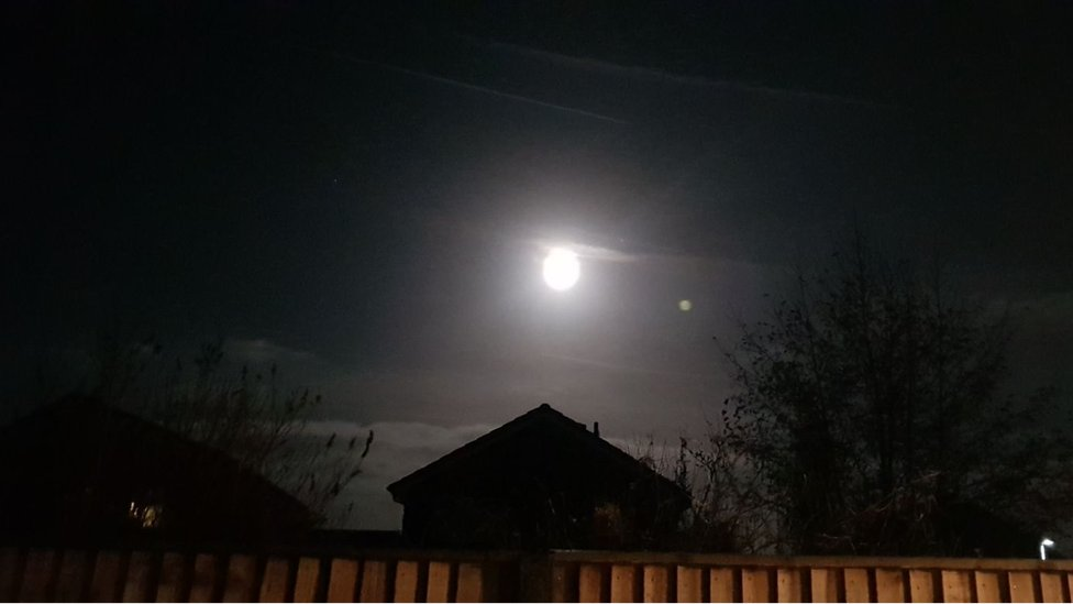 An image of the supermoon bright above a rooftop