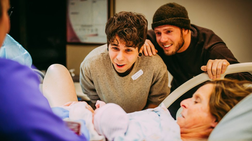 Parents Elliot Dougherty and Matthew Eledge meet their newborn daughter at the hospital.