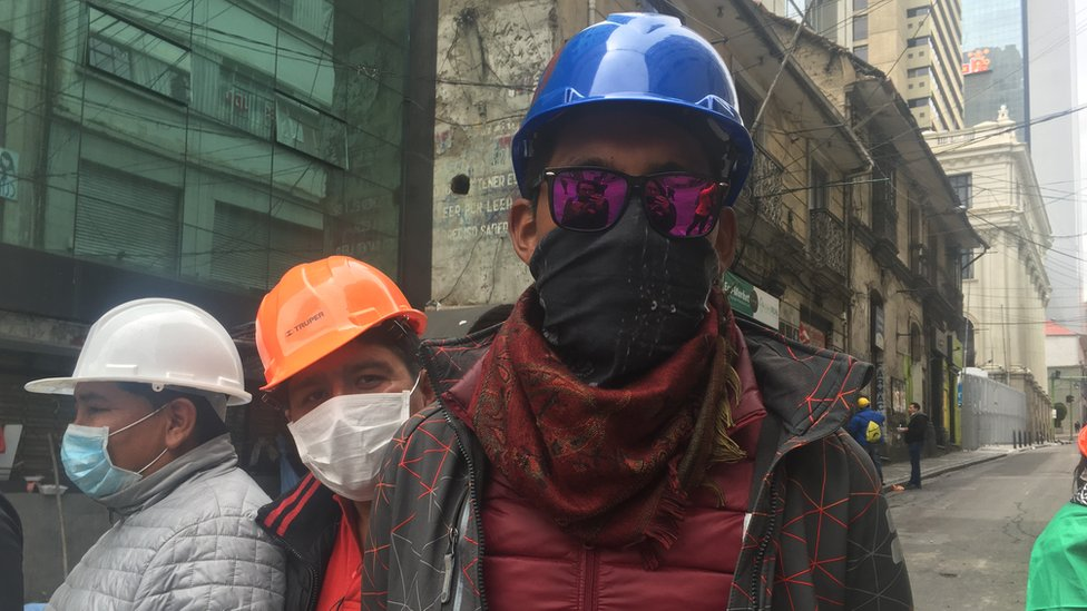 Protester Marcos poses for a photograph in a blue helmet and sunglasses