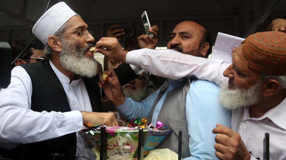 Siraj ul Haq, the head of the conservative Jamaat-e-Islami group, shares sweets with opposition supporters after the Supreme Court verdict to disqualify Pakistan's PM Nawaz Sharif, 28 July, 2017