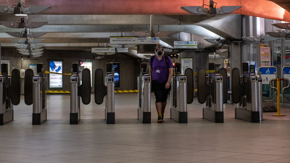 A man wearing a full face mask walks out of Westminster underground train station on April 17, 2020 in London, United Kingdom