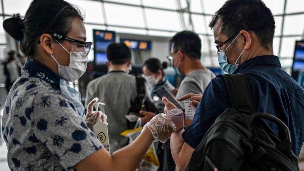 Funcionária de aeroporto em Wuhan checa temperatura de passageiro, ambos de máscaras