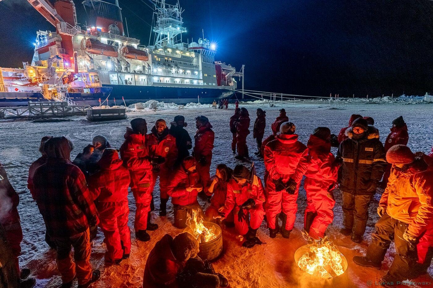 Researchers gathered around camp fire. Polarstern is seen in the background.