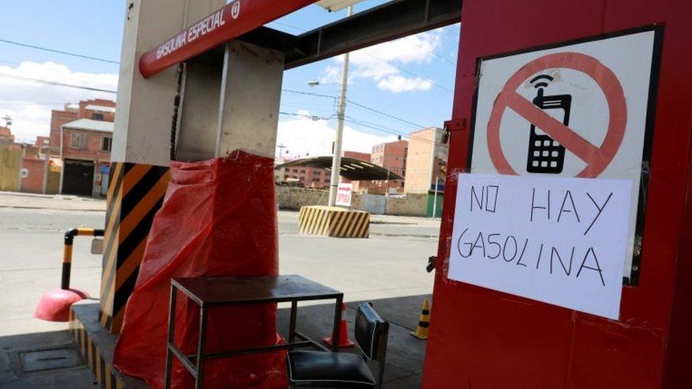 A placard is seen at a closed gas station in El Alto, near La Paz, Bolivia