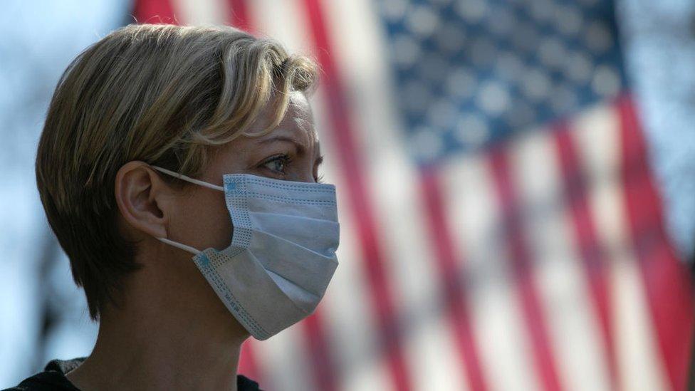 Mujer con mascarilla frente a bandera estadounidense.