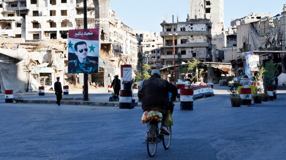 A Syrian rides a bicycle towards a check point amid the ruins of buildings in the old city of Homs (7 December 2015)