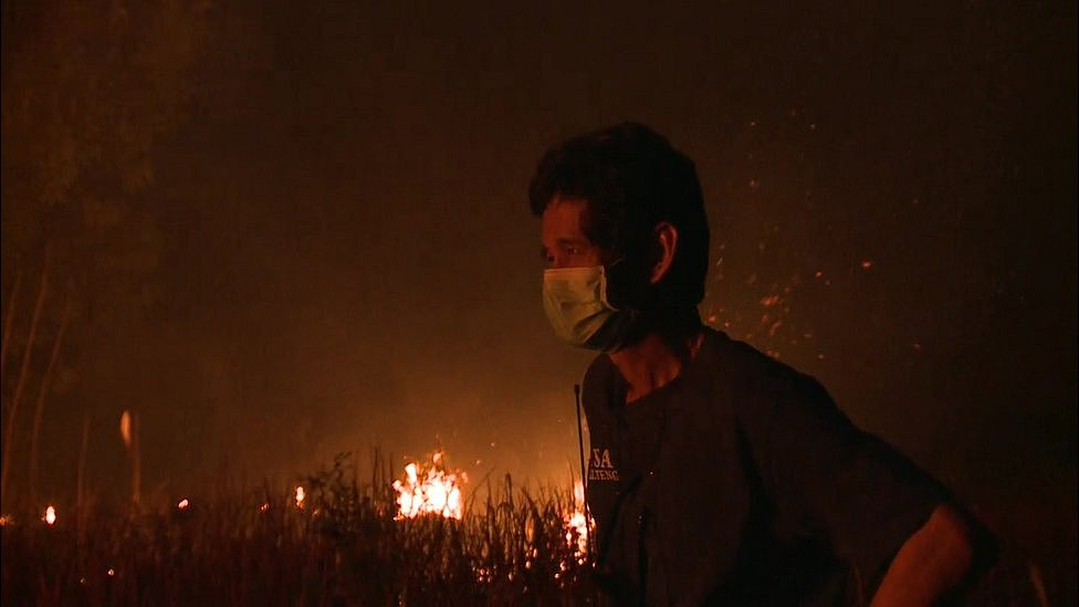 A man fighting the fires watches them burn
