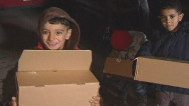 Refugee children holding gifts donated by local charity in Mulheim, Germany