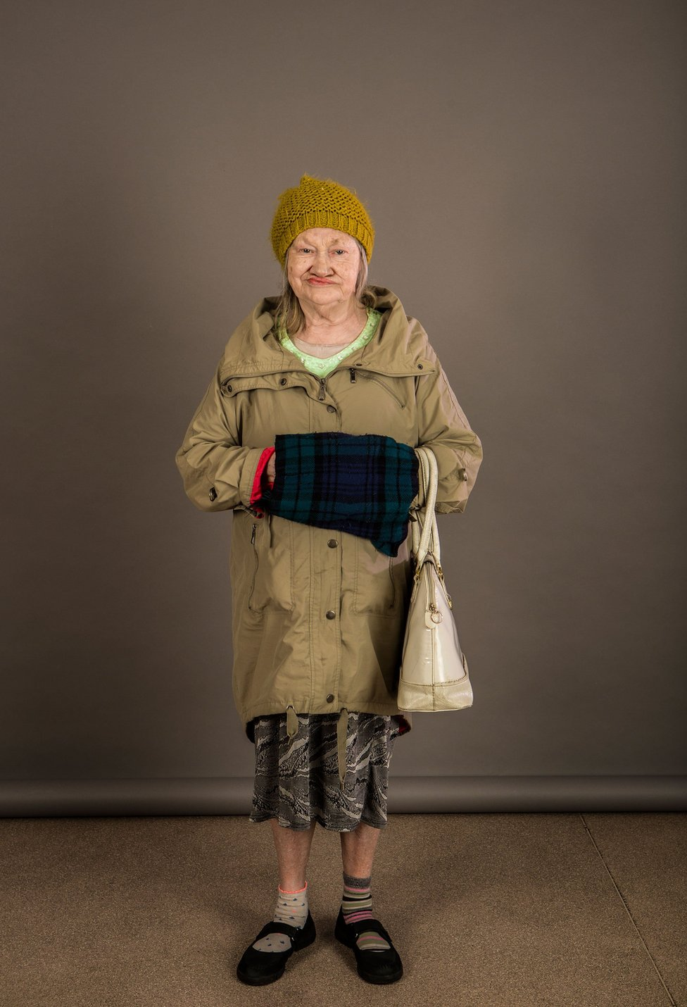 An elderly lady wearing a woolly hat and coat