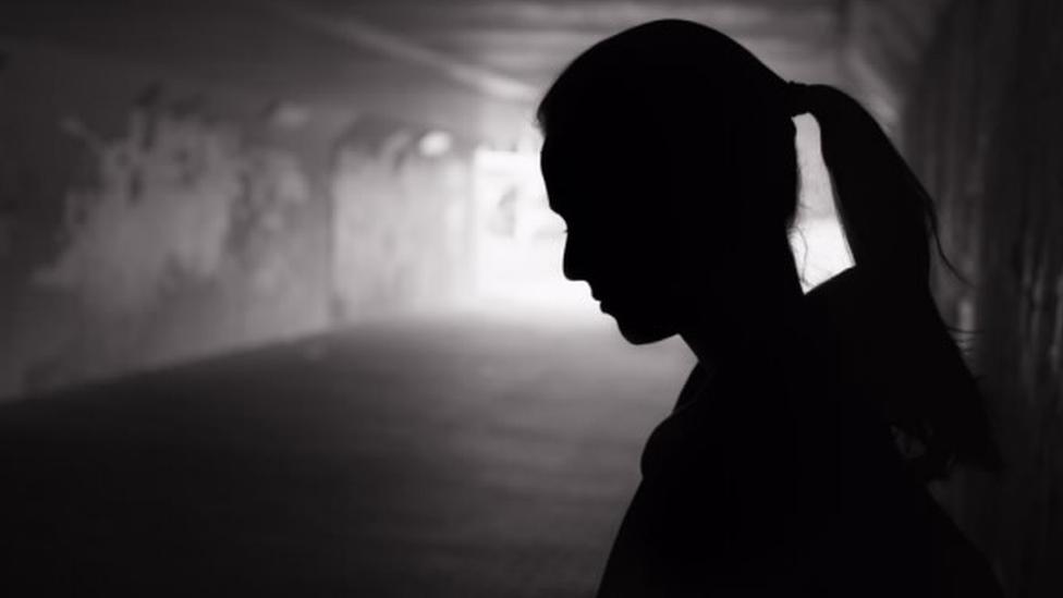 Una mujer en la oscuridad.