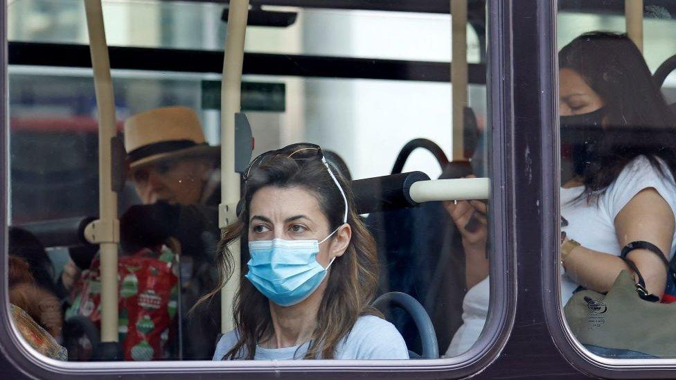 Mulher olha pela janela de um ônibus em Londres