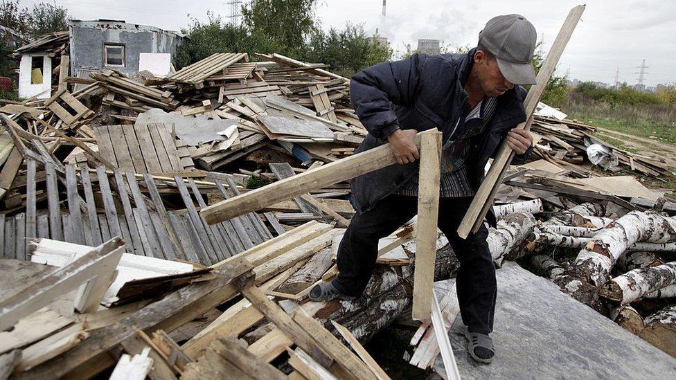 Un trabajador de Tayikistán recoge madera cerca de Moscú.