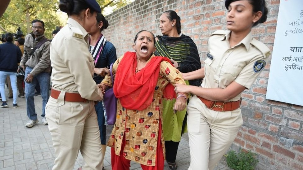 Gujarat Police officials detain a demonstrator during a peaceful protest against the Indian government's Citizenship Amendment Bill outside Indian Institute of Management (IIM) in Ahmedabad on Monday