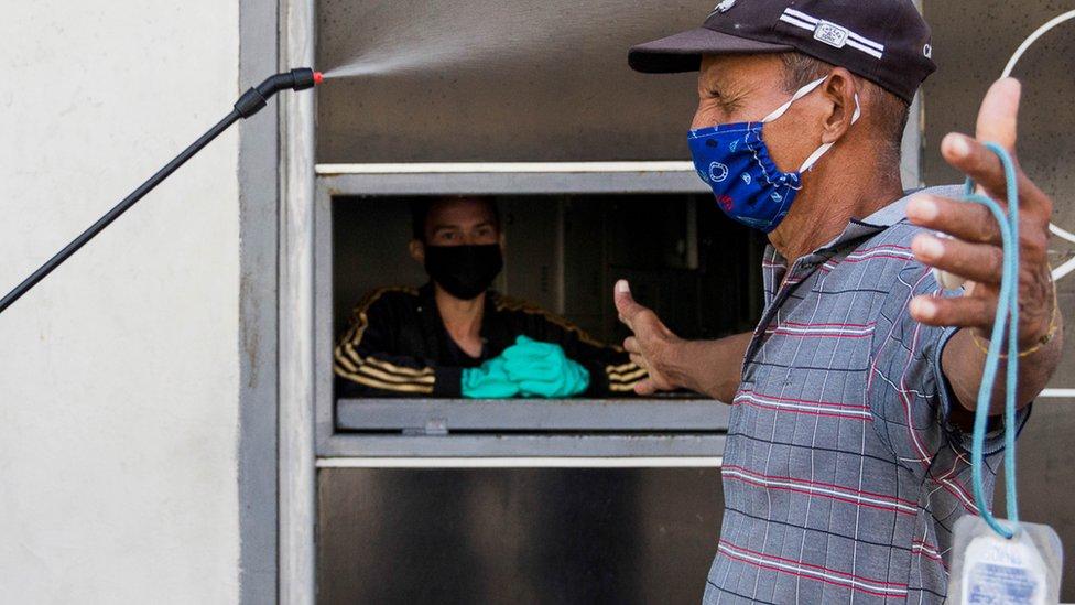 Un hombre se desinfecta antes de entrar a un negocio en Maracaibo.