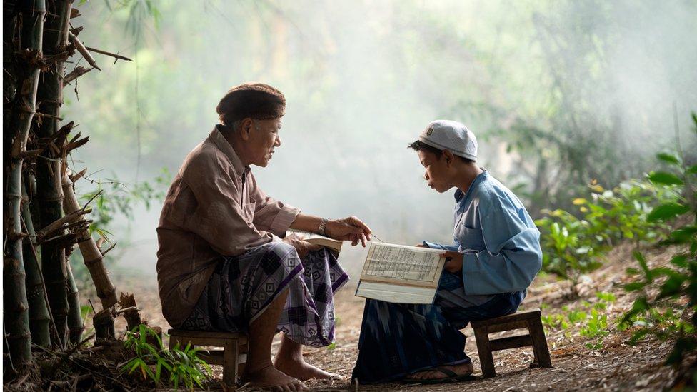 Un niño en Indonesia aprende a leer el Corán con su abuelo.