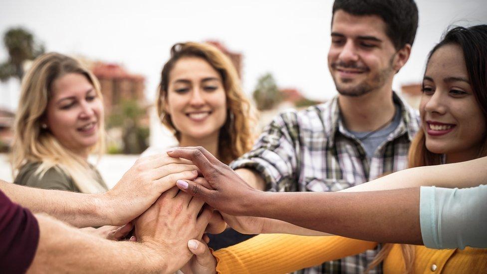 Grupo de hombres y mujeres juntando sus manos.