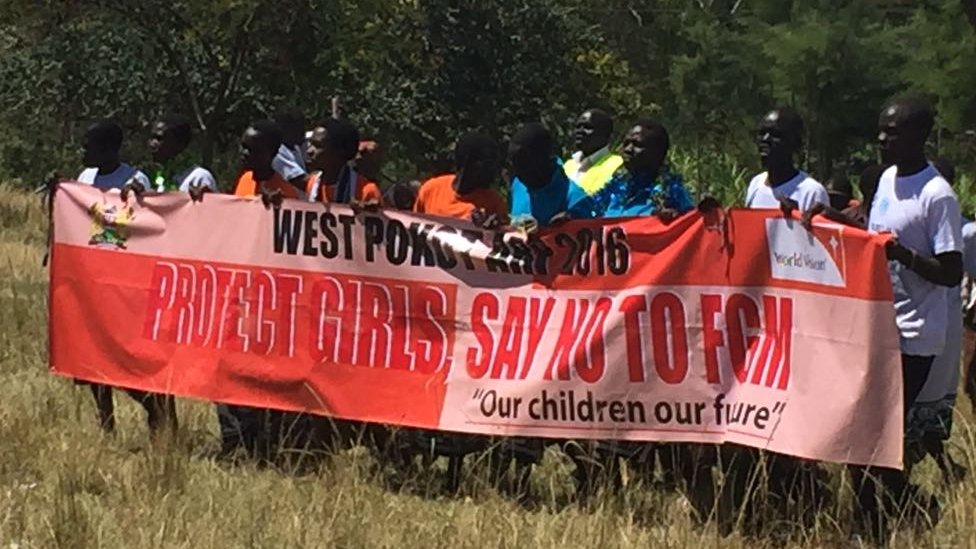 Group of men holds banner reading: Pokot County - say no to FGM - our children our future