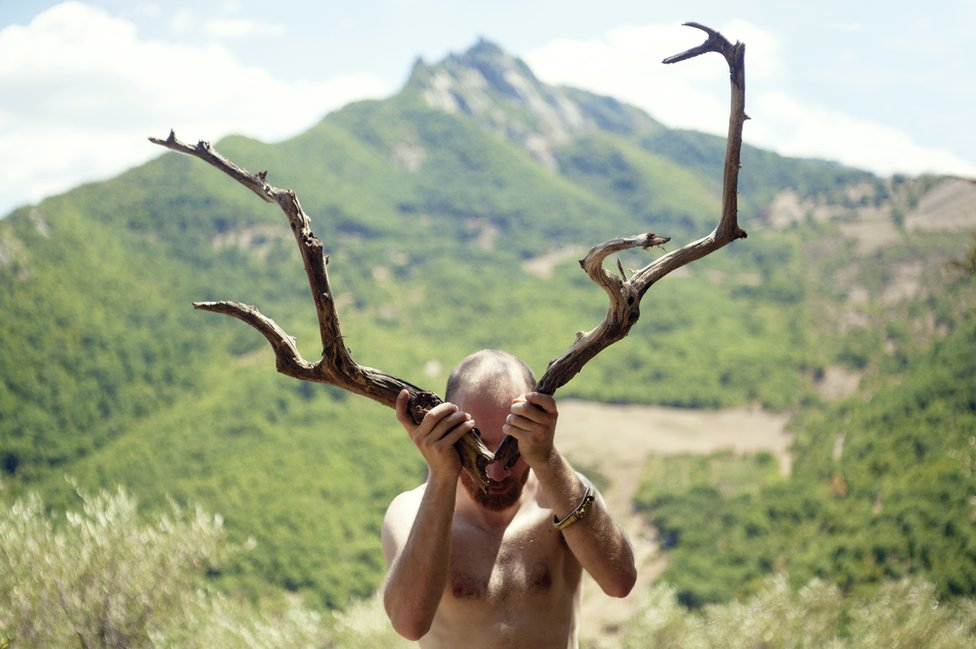 A man holds two antlers up to cover his face.