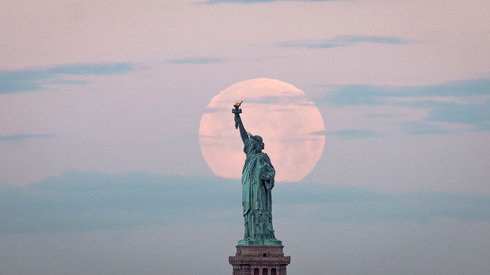 "May""s full Moon, known as the Full Flower Moon and is the last supermoon of the year, sets behind the Statue of Liberty in New York City"