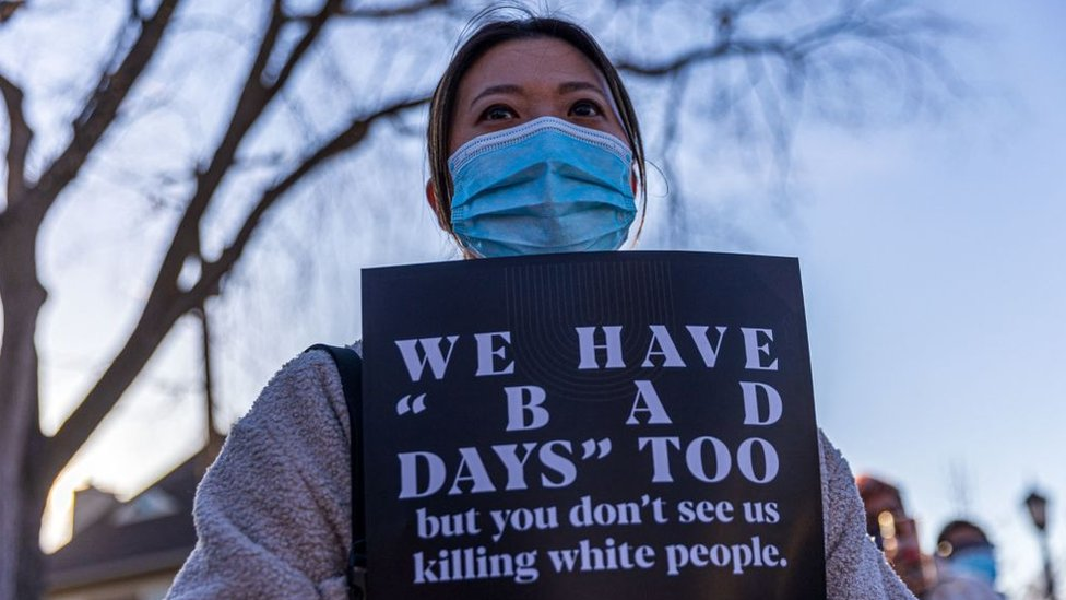 """Hilary Hill Nc holds sign during the """"Asian Solidarity March"""" rally against anti-Asian hate in response to recent anti-Asian crime on March 18, 2021 in Minneapolis, Minnesota"""