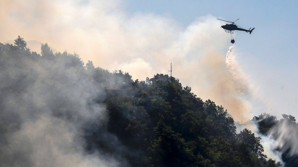 A helicopter drops water as firefighters work to extinguish a wild fire in Mount Dajti, east of capital Tirana, 4 August 2017