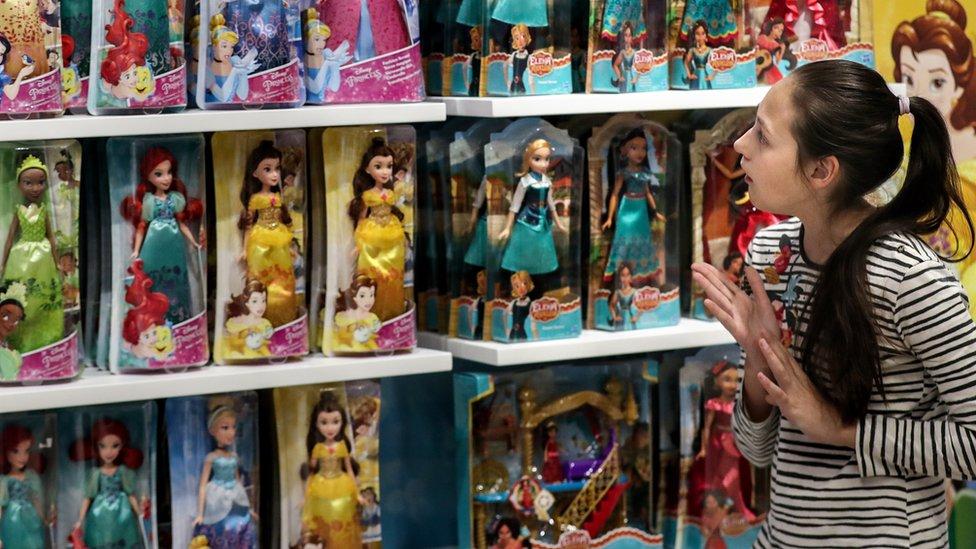 A girl looking at Disney Princess dolls