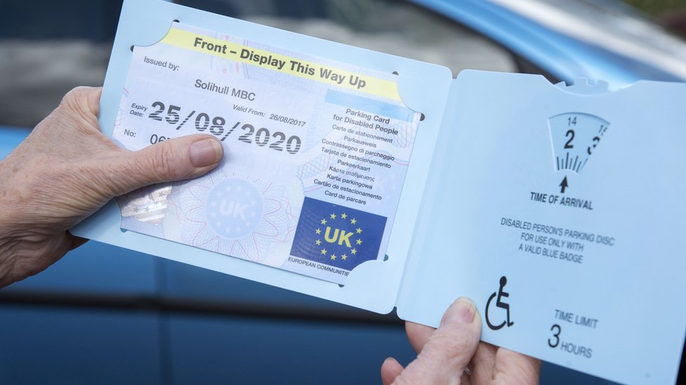 A woman showing her disable person's parking permit
