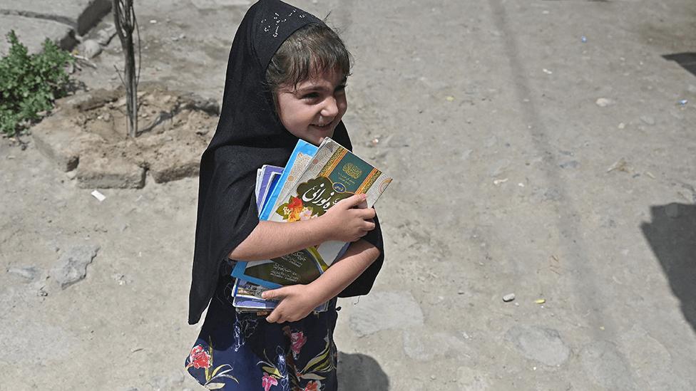 فتاة تحمل كتباً في كابول في 12 يوليو/تموز 2021