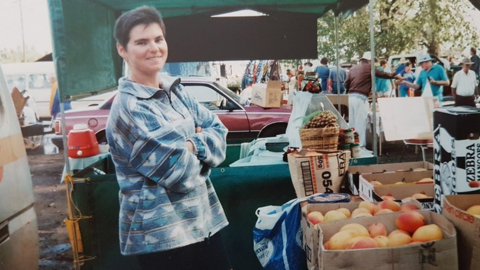 A woman stands at a market with her arms crossed, smiling