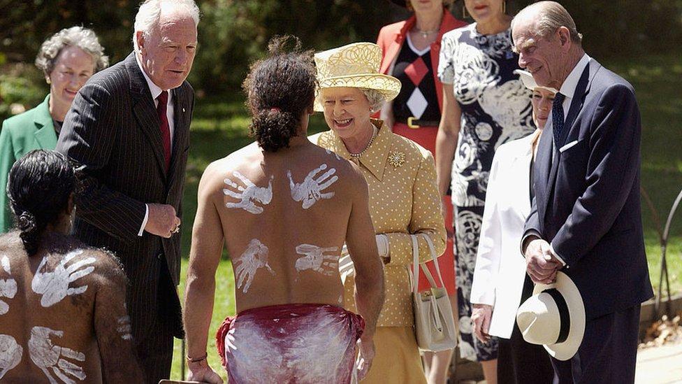 الملكة إليزابيث الثانية و زوجها الأمير فيليب دوق أدنبره وممثلهم الحاكم العام في أستراليا بيتر هولينغوورث يلتقون بالراقصين من الأستراليين الأصليين خلال مراسم احتفالية بمناسبة بدء الزيارة الملكية إلى أستراليا ، 27 فبراير/شباط 2002 في أديلايد.