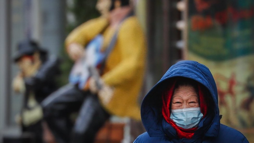 A woman wearing protective face mask walks on the street during pandemic of SARS-CoV-2 coronavirus in Moscow, Russia 18 November 2020