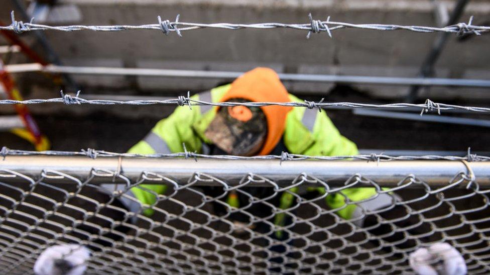 Un hombre instalando una valla metálica