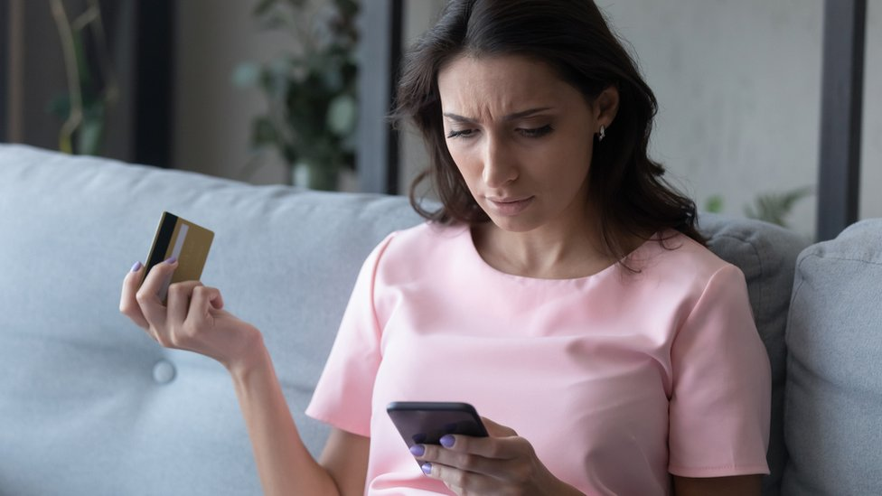 Una mujer revisa en su móvil las transacciones sospechosas de su tarjeta de crédito