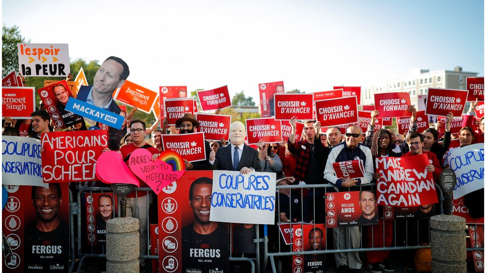 A crowd of partisan supporters await the arrival of the party leaders to the debate venue