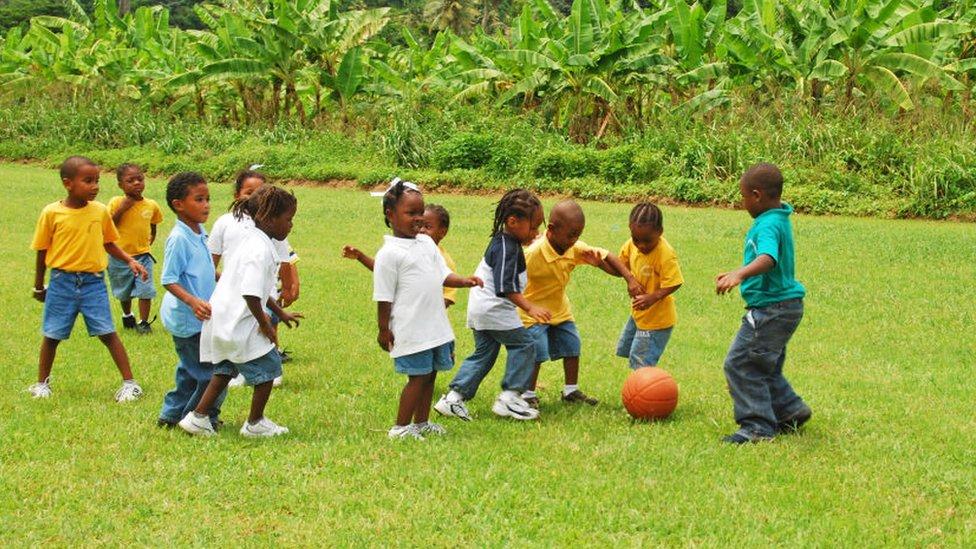 Niños y niñas jugando al fútbol.