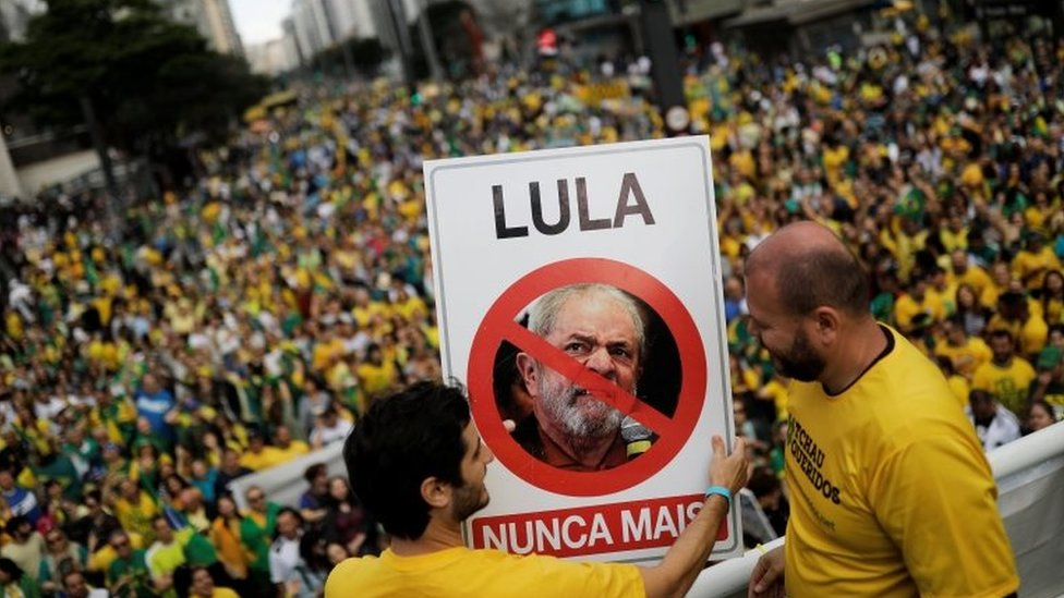 "Supporters of Jair Bolsonaro hold a sign with the image of former Brazilian President Luiz Inácio Lula da Silva reading ""Lula, never again"""