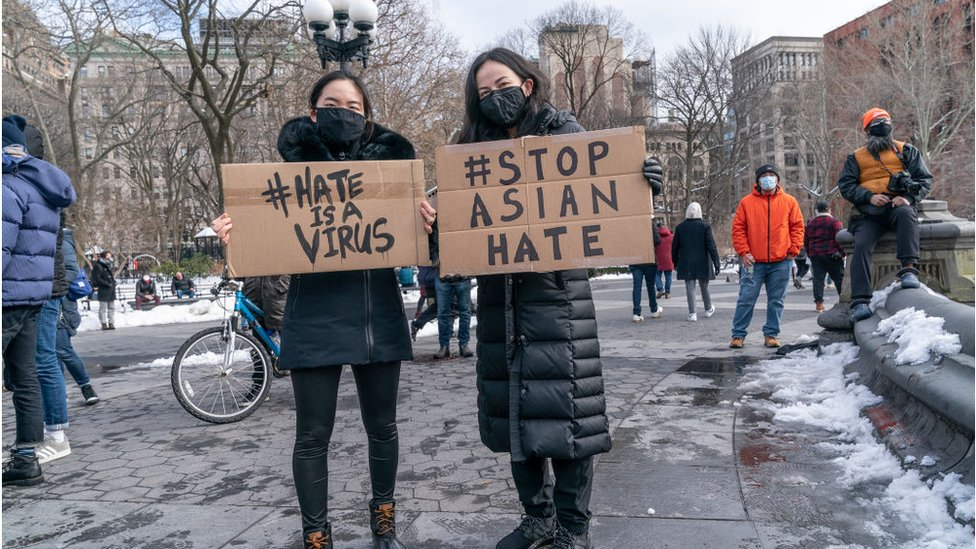 Two people holding stop Asian hate signs
