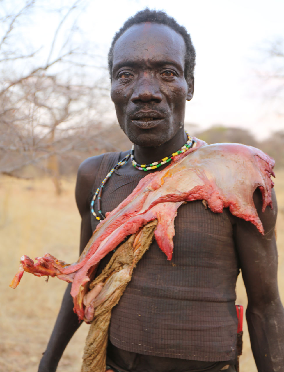 Hadza man carrying meat