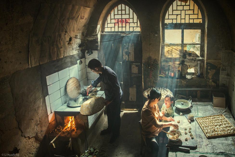 Familia preparando comida en el interior, con rayos de sol brillando a través de las ventanas