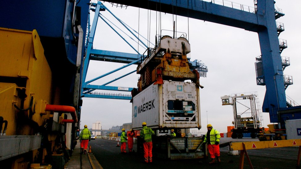 Staff unload shipping containers at Tilbury Dock