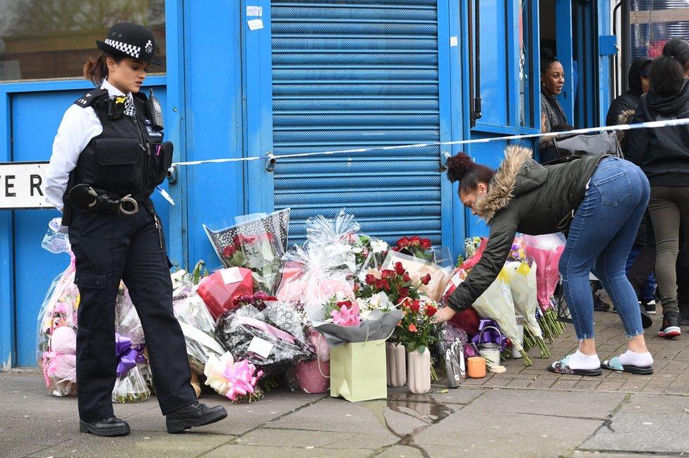 امرأة تضع زهورا في شارع في حي توتنهام شمالي العاصمة البريطانية لندن حيث توفي تانيشا ميلبورن الذي كان في السابعة عشرة بعد إطلاق النار عليه. وعلى بعد ميلين في حي ولتامستو عثر على صبي آخر مصاب بجروح سببتها طلقات نارية، يرقد إلى جانب صبي ثالث في الـ15 مصاب بجروح سببتها طعنات سكين.