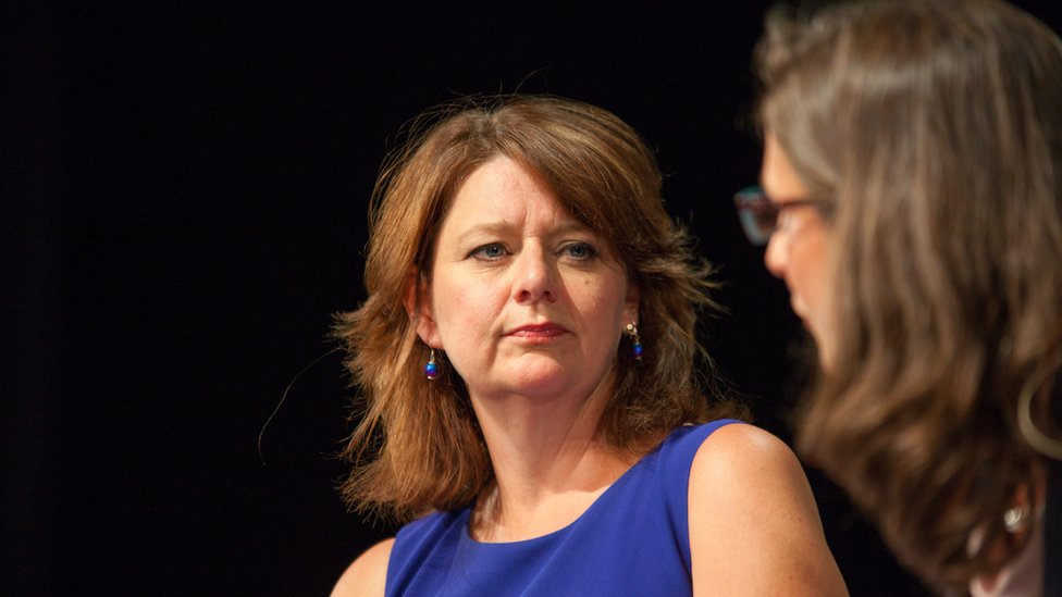 Close up of Leanne Wood looking like she is listening to another woman speaking during a debate. She is wearing blue dress and is against a black back drop