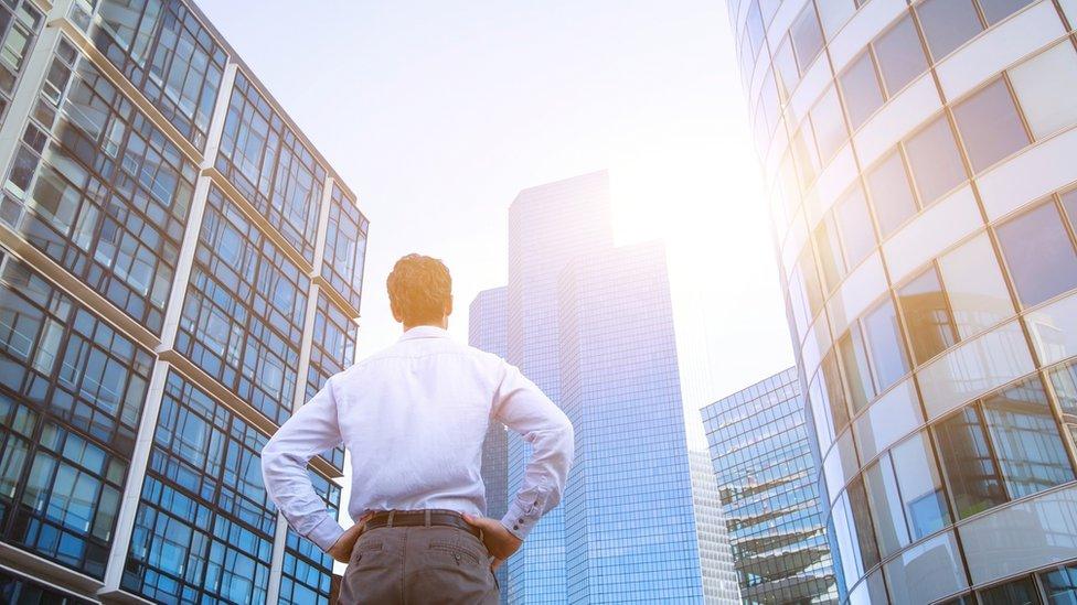 İş kulelerinin önünde bir adam görülüyor