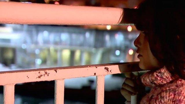 Migrant girl looks through railings