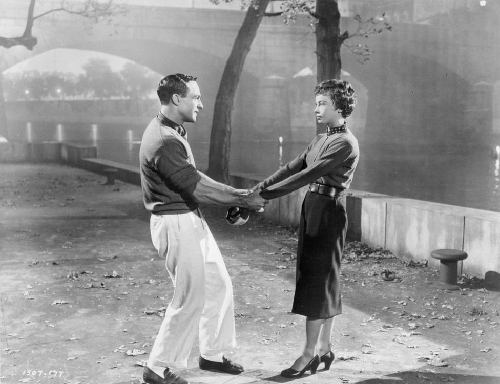 Gene Kelly hold Leslie Caron's arms in a scene from An American In Paris