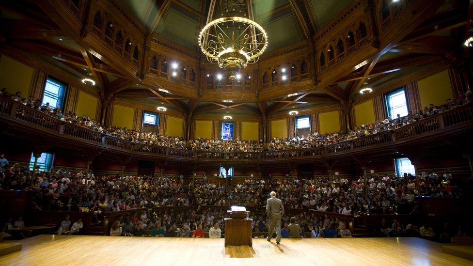 Michael Sandel dando una clase a cientos de alumnos en un teatro de Harvard.